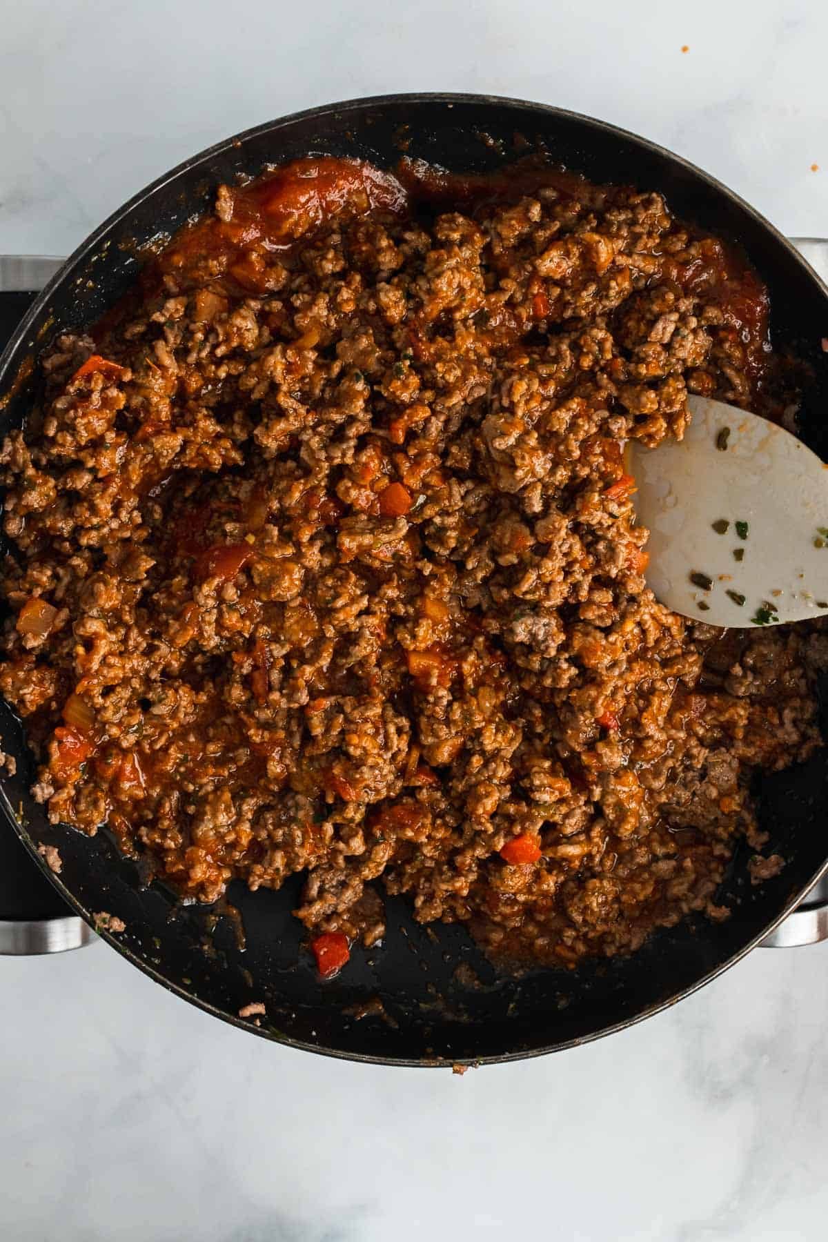 Tomato sauce stirred into the cooked ground beef in the skillet, as seen from above