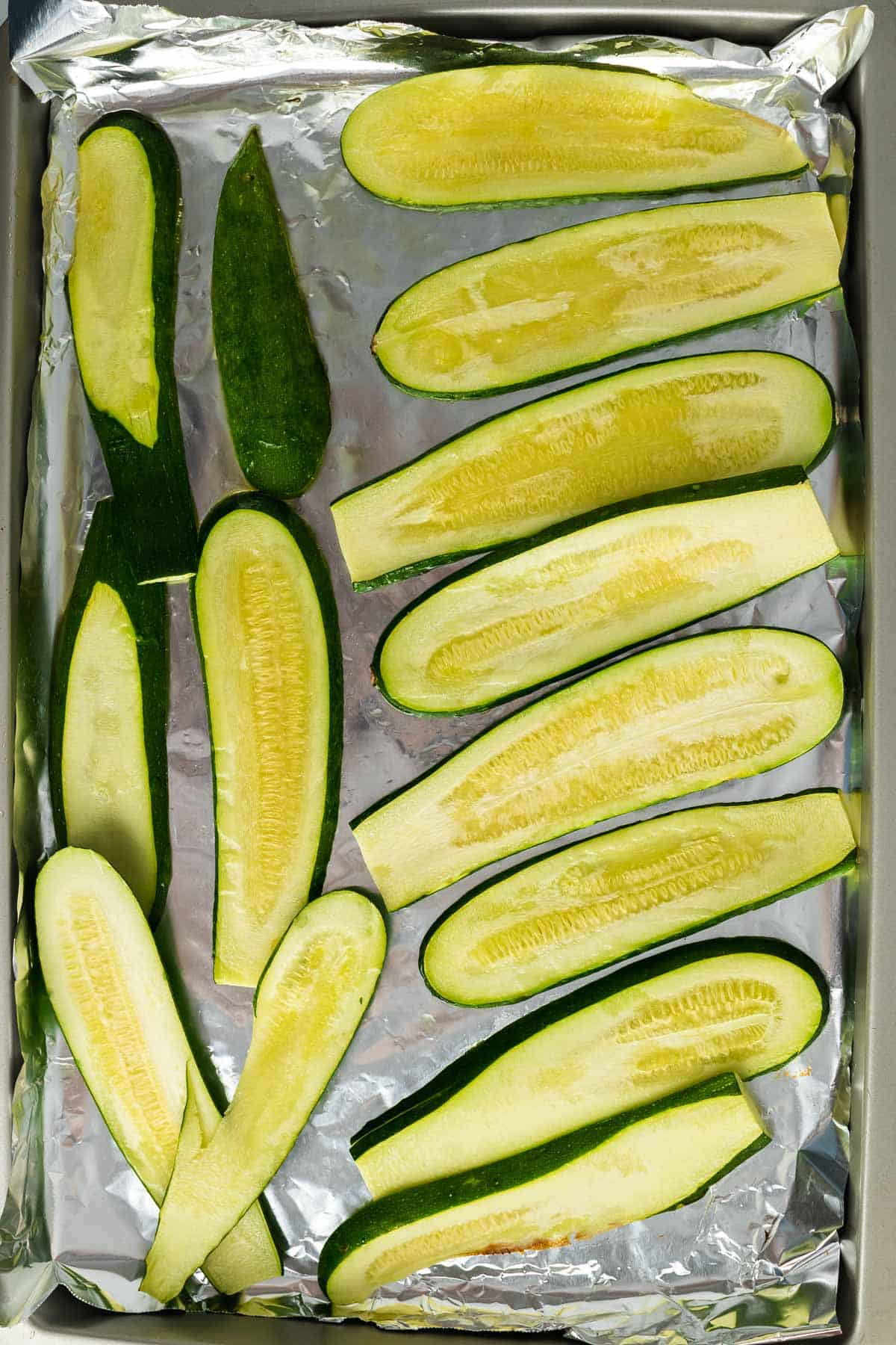 Cooked zucchini slices on a baking sheet lined with foil, as seen from above