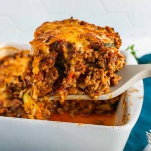 A slice of low-carb lasagna being lifted by a spatula out of the baking dish