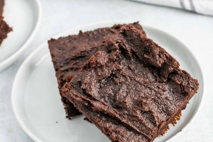 Close-up of two avocado brownies on a small white plate