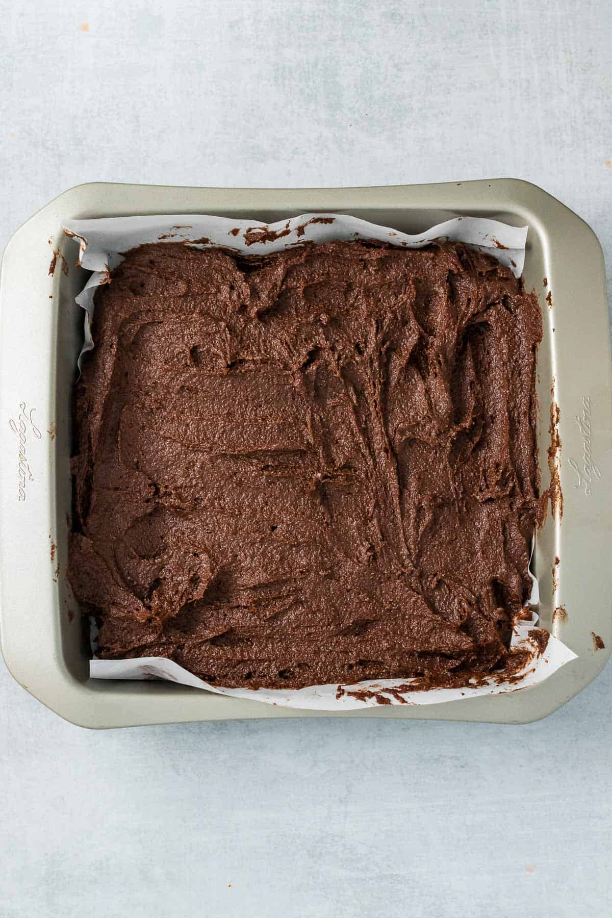 Brownie batter in a square baking dish over parchment paper, ready to bake