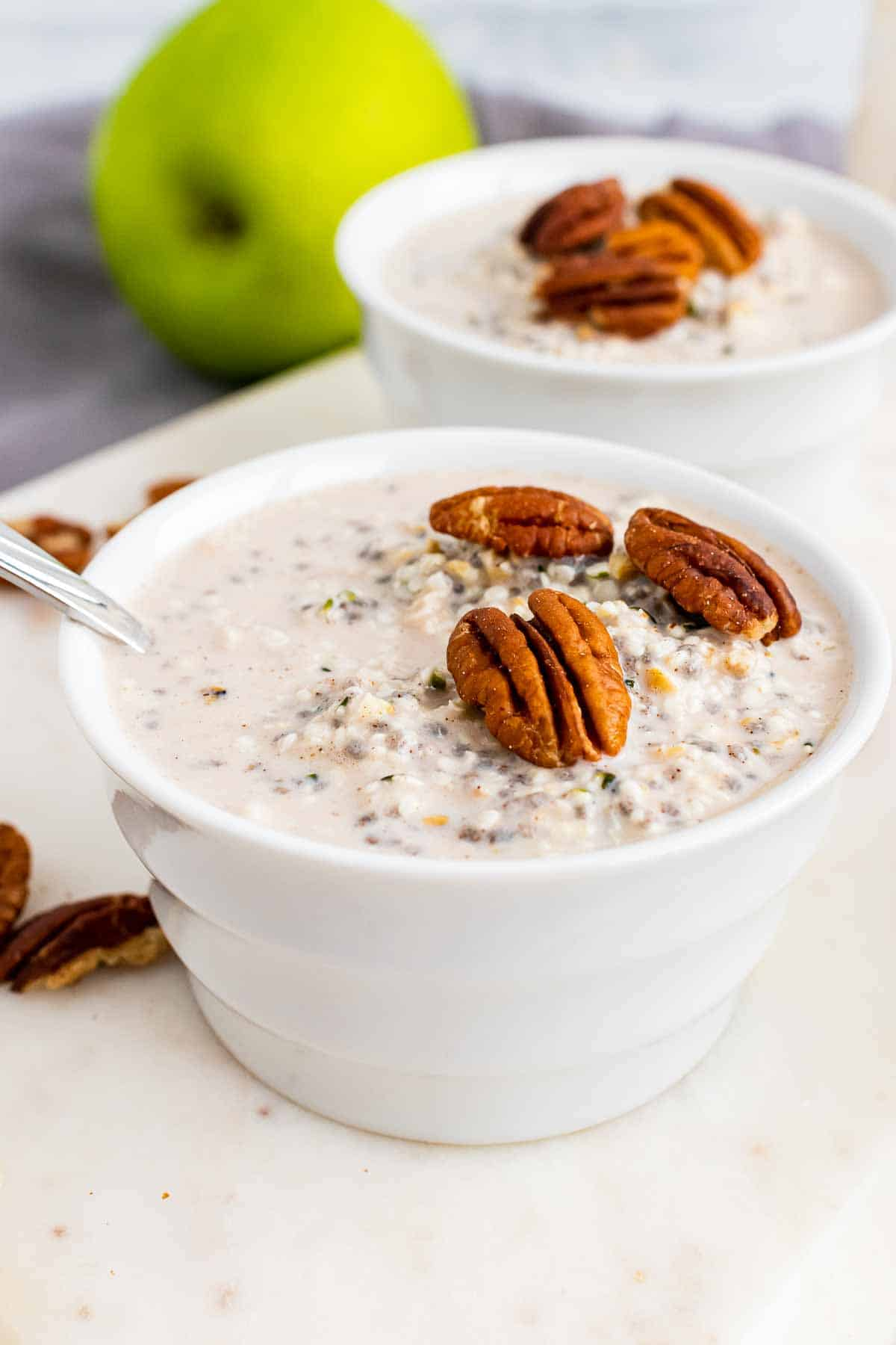Finished oats topped with pecans in two white bowls on a white serving tray