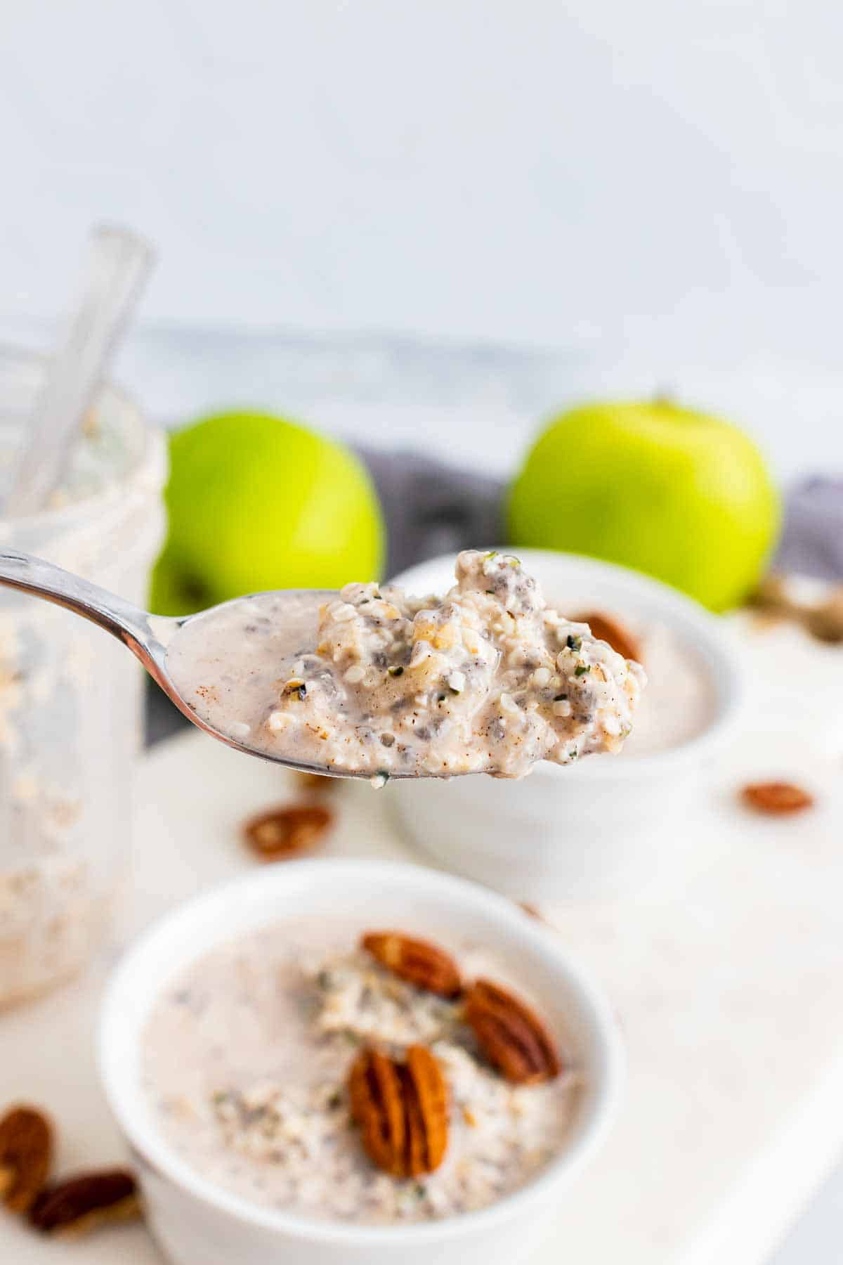 A spoonful of oats with two bowls of oats topped with pecans, an empty glass jar, and two apples in the background