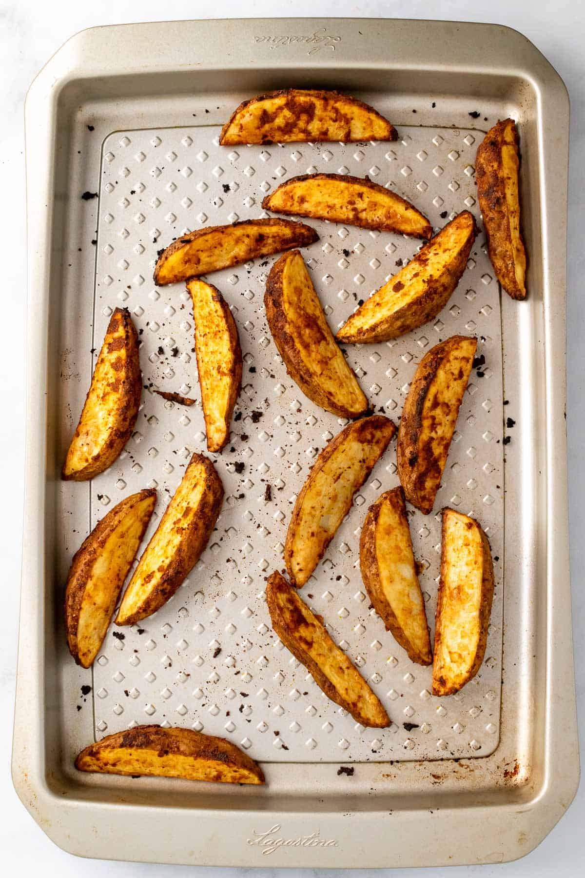 Baked French fries on a aluminum baking sheet