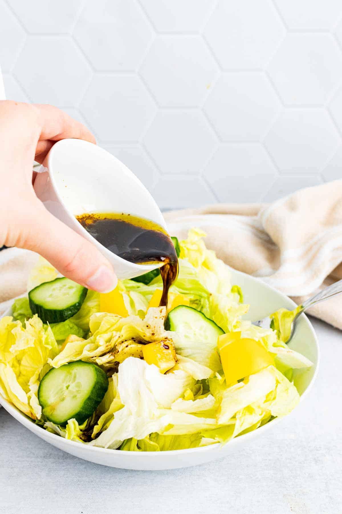 Hand pouring balsamic vinaigrette over a salad