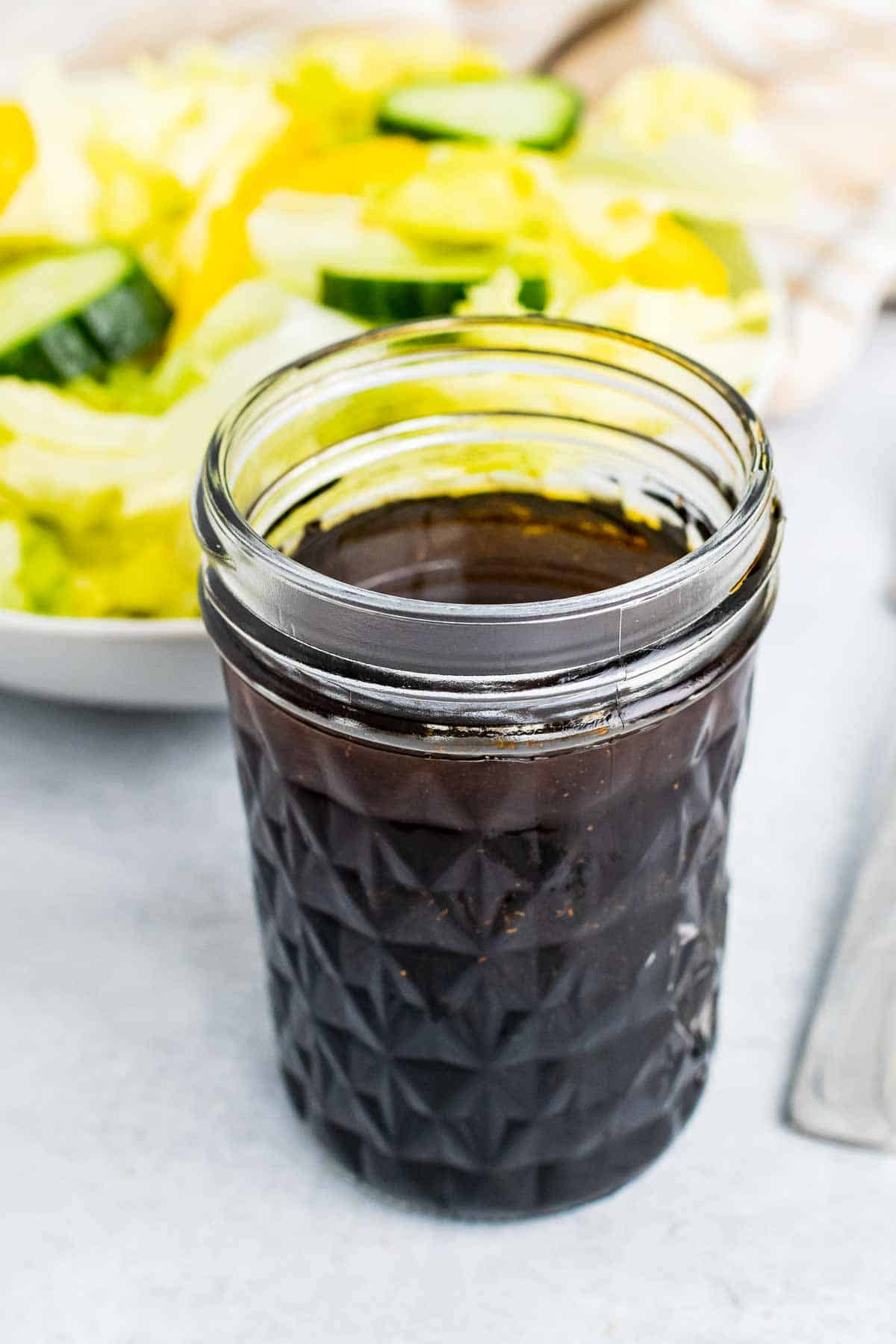Glass of balsamic vinaigrette in front of salad bowl