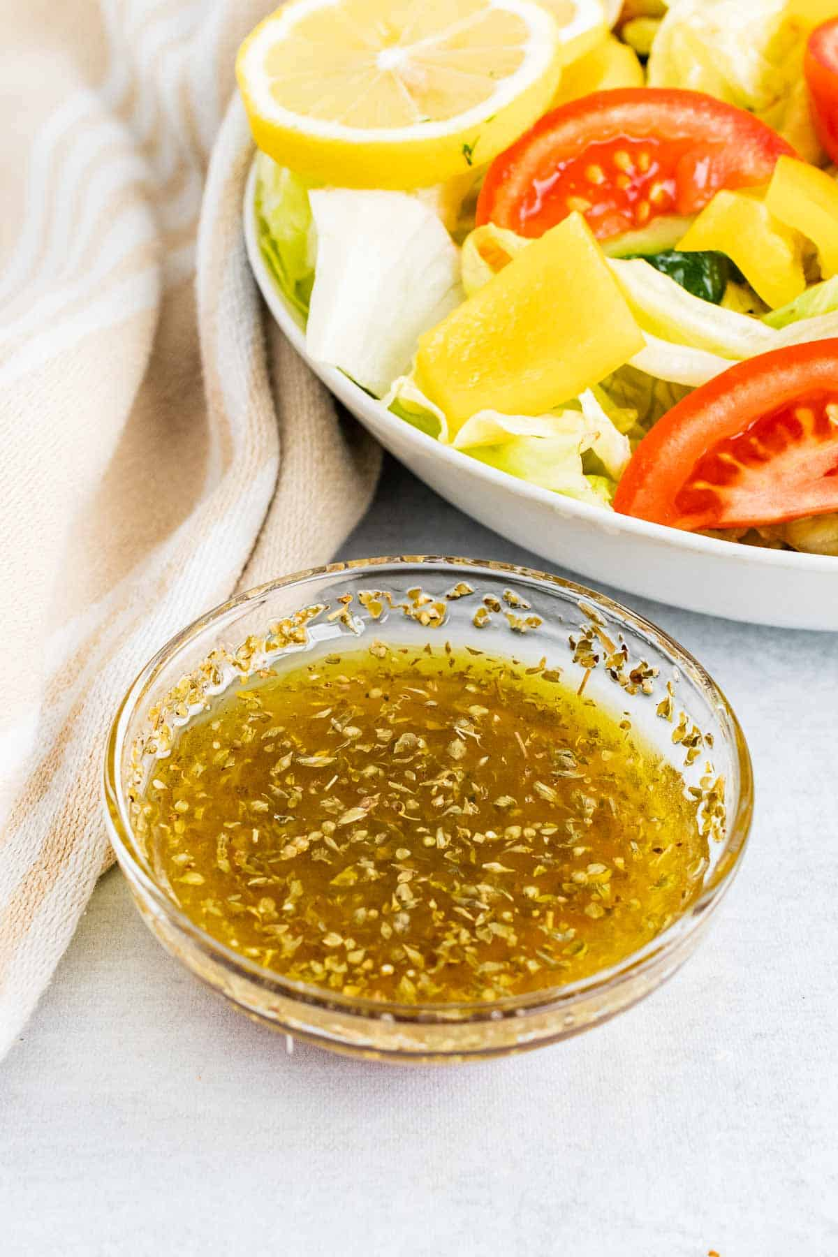 Small glass ramekin with dressing in front of salad bowl
