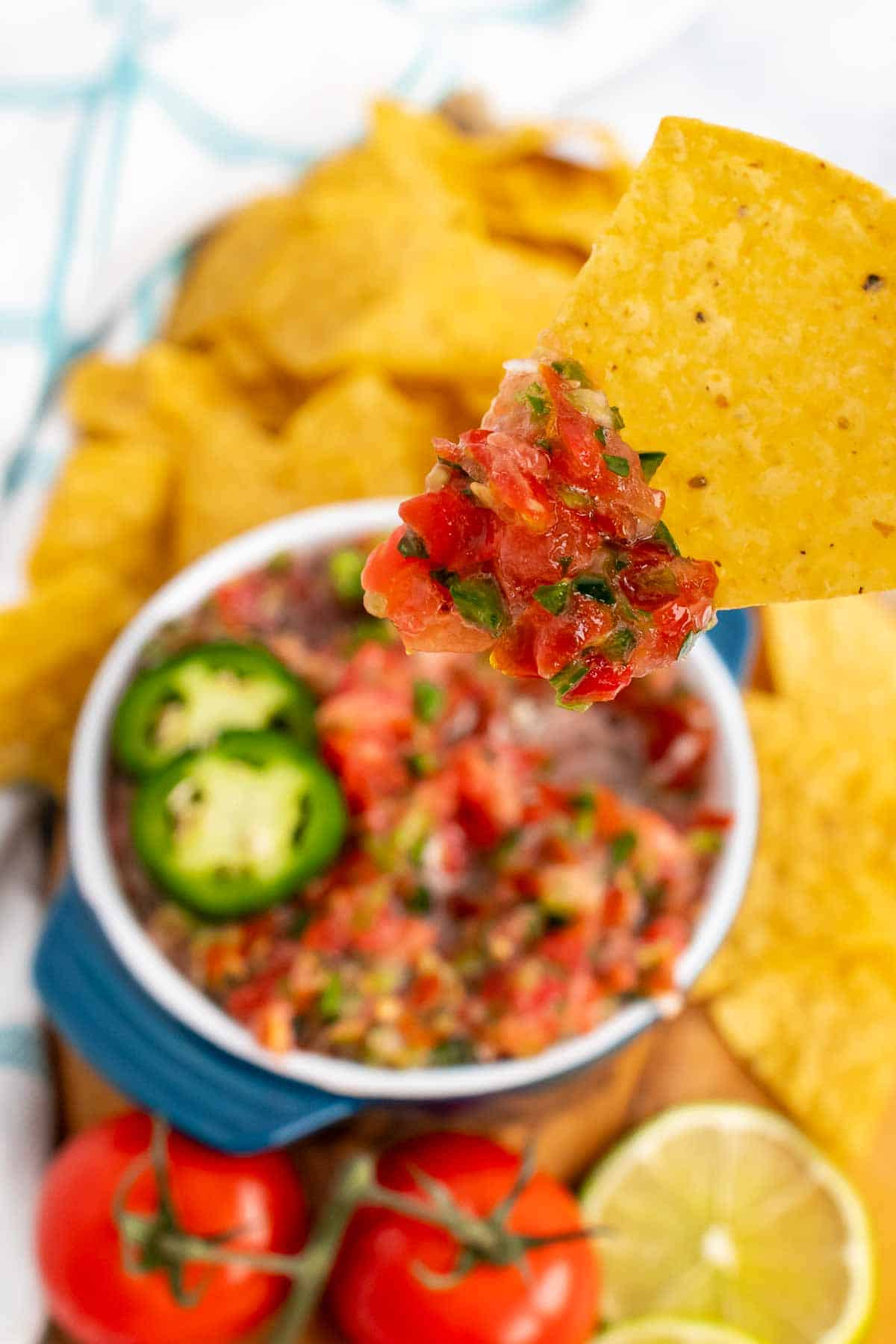 Chip with salsa over a bowl of salsa