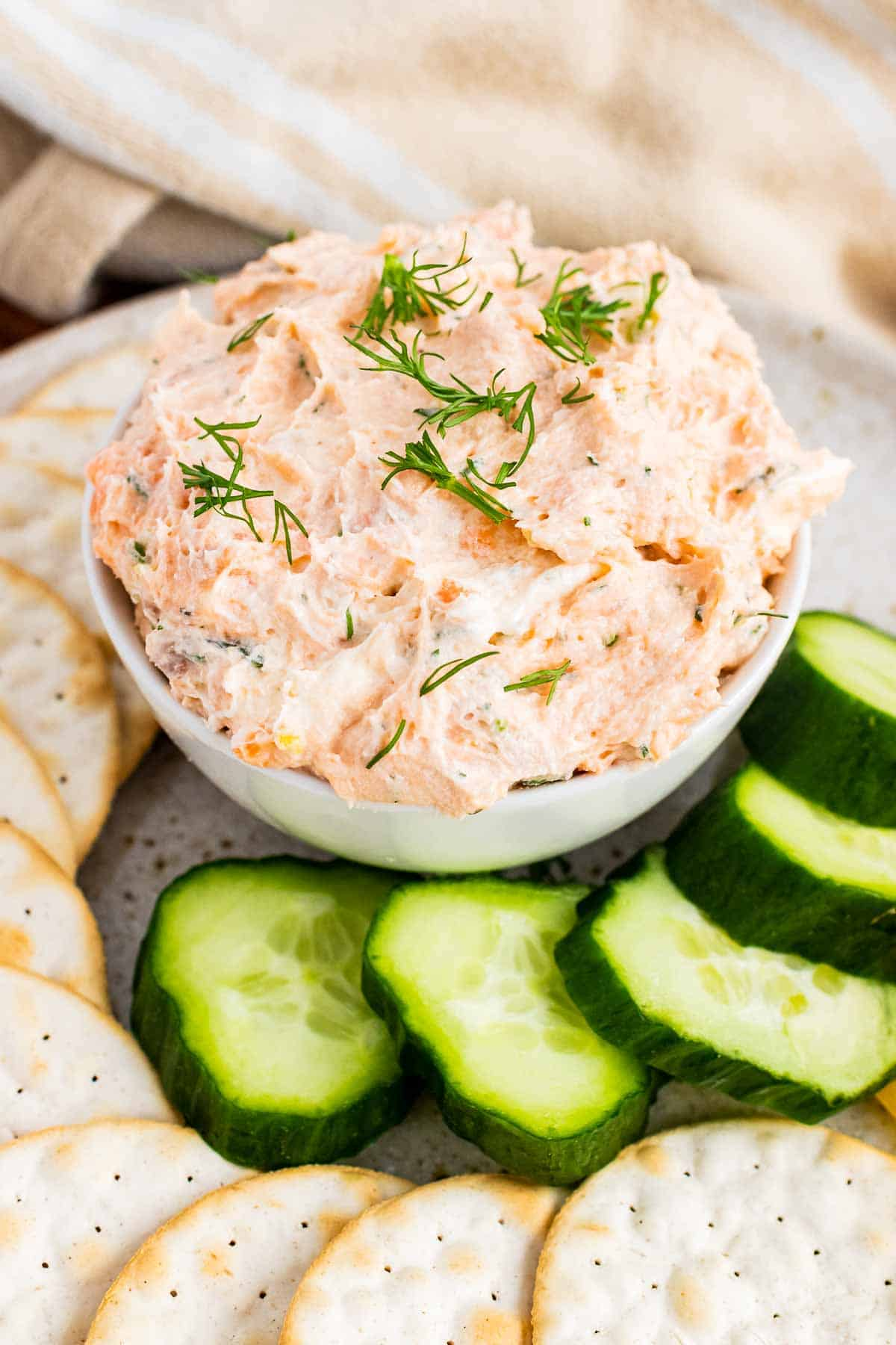 Bowl of smoked salmon spread with crackers and cucumbers