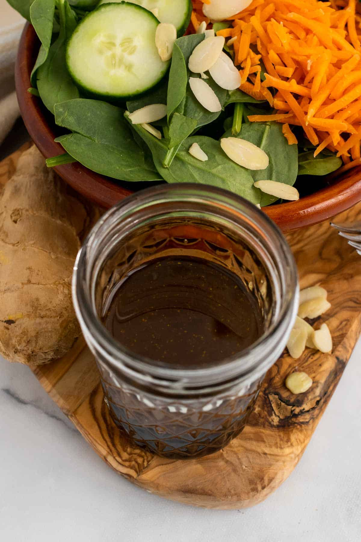 Glass of vinaigrette in front of salad bowl