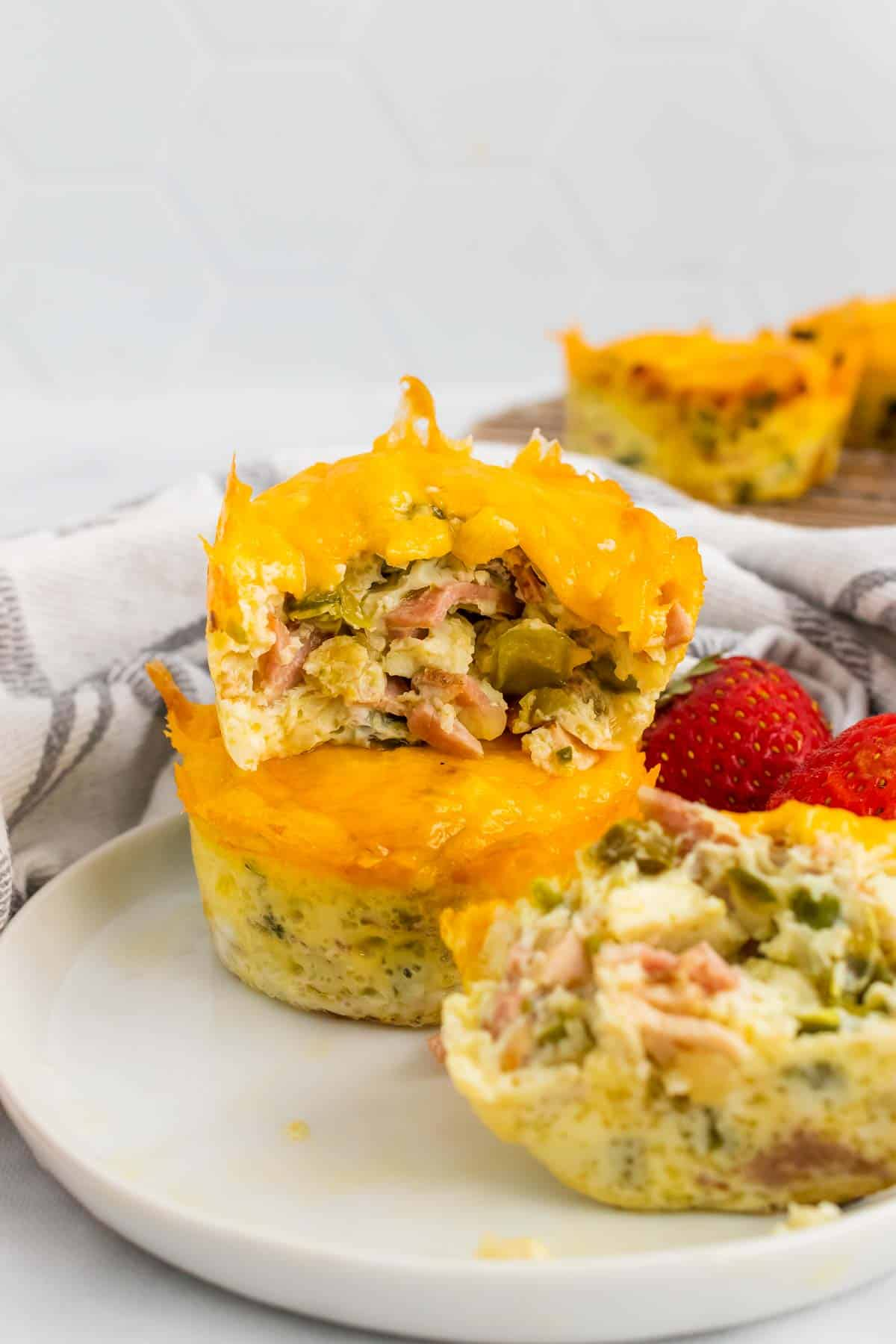 Three bacon and egg muffins on a plate