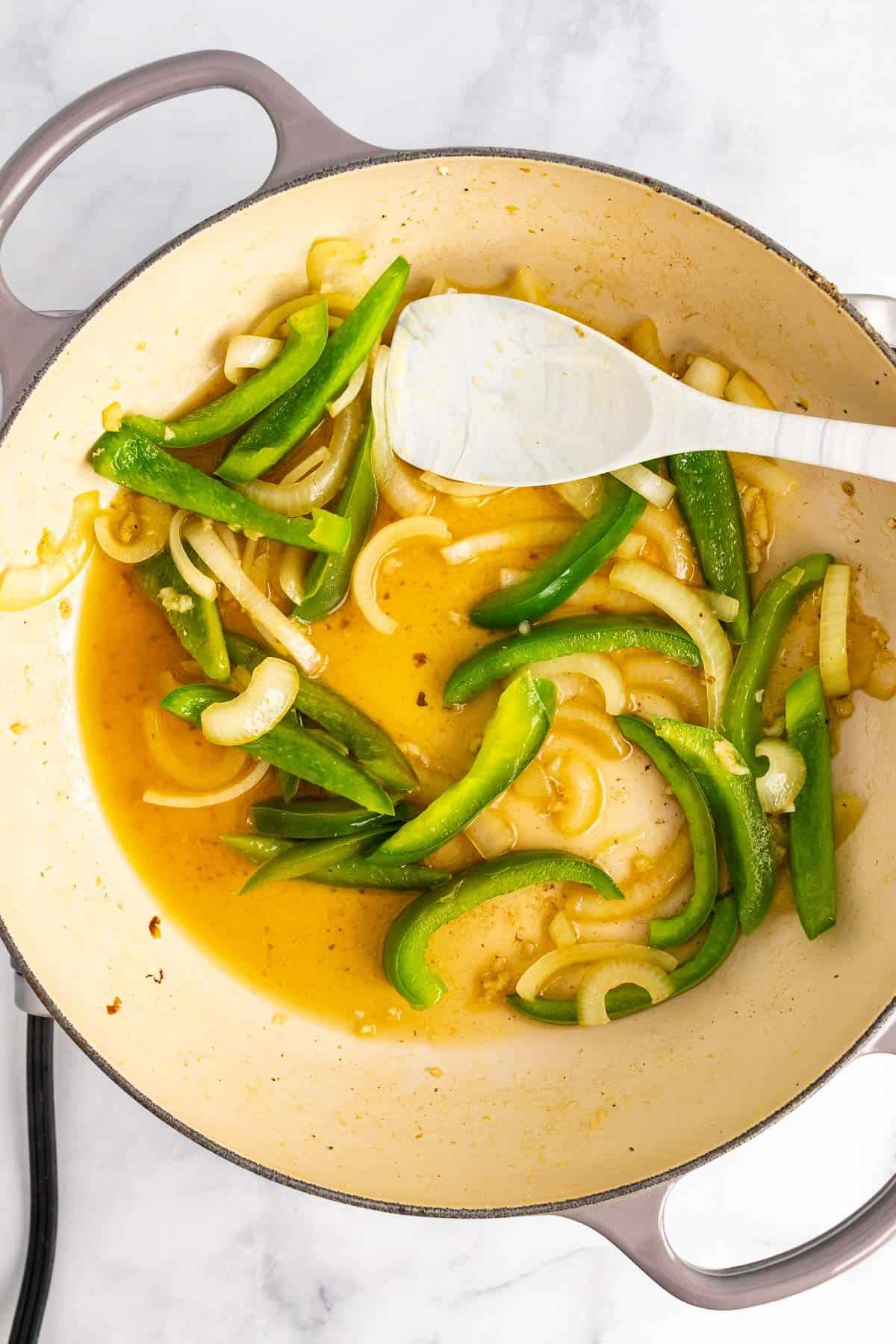 Vegetables and wine simmering in pan