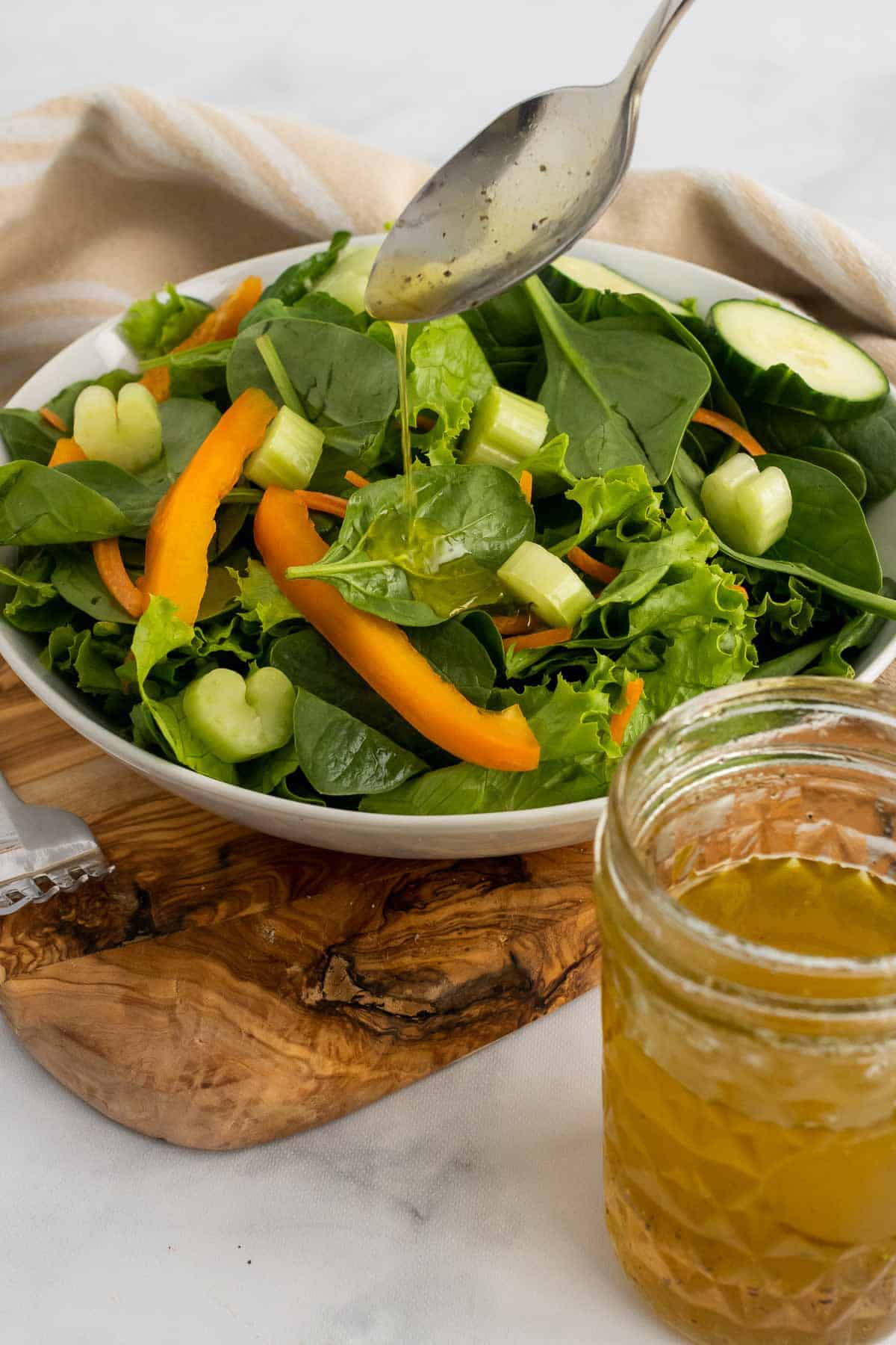 Spoon with fruity white balsamic vinaigrette over a salad bowl