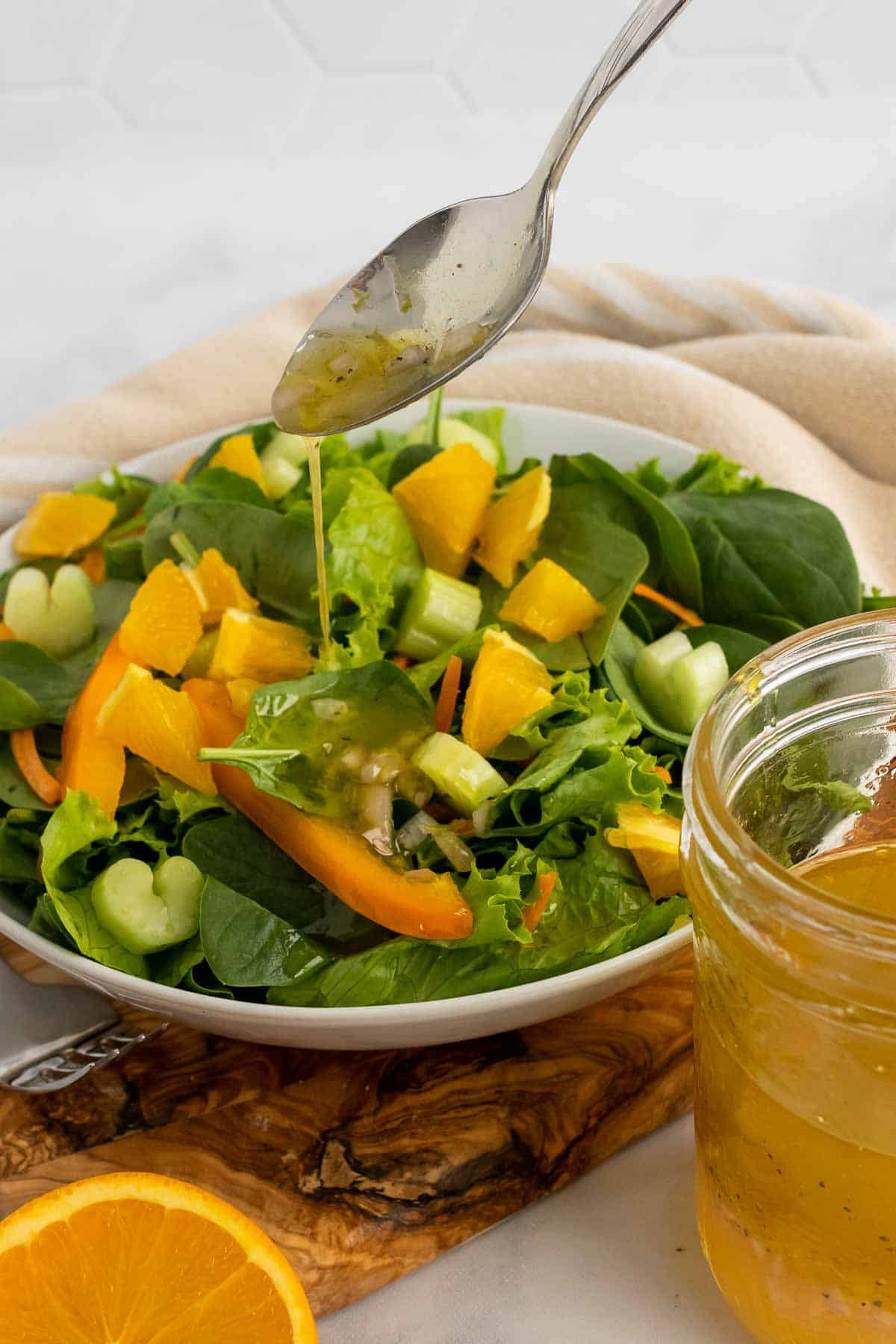 Spoon drizzling vinaigrette over a spinach salad