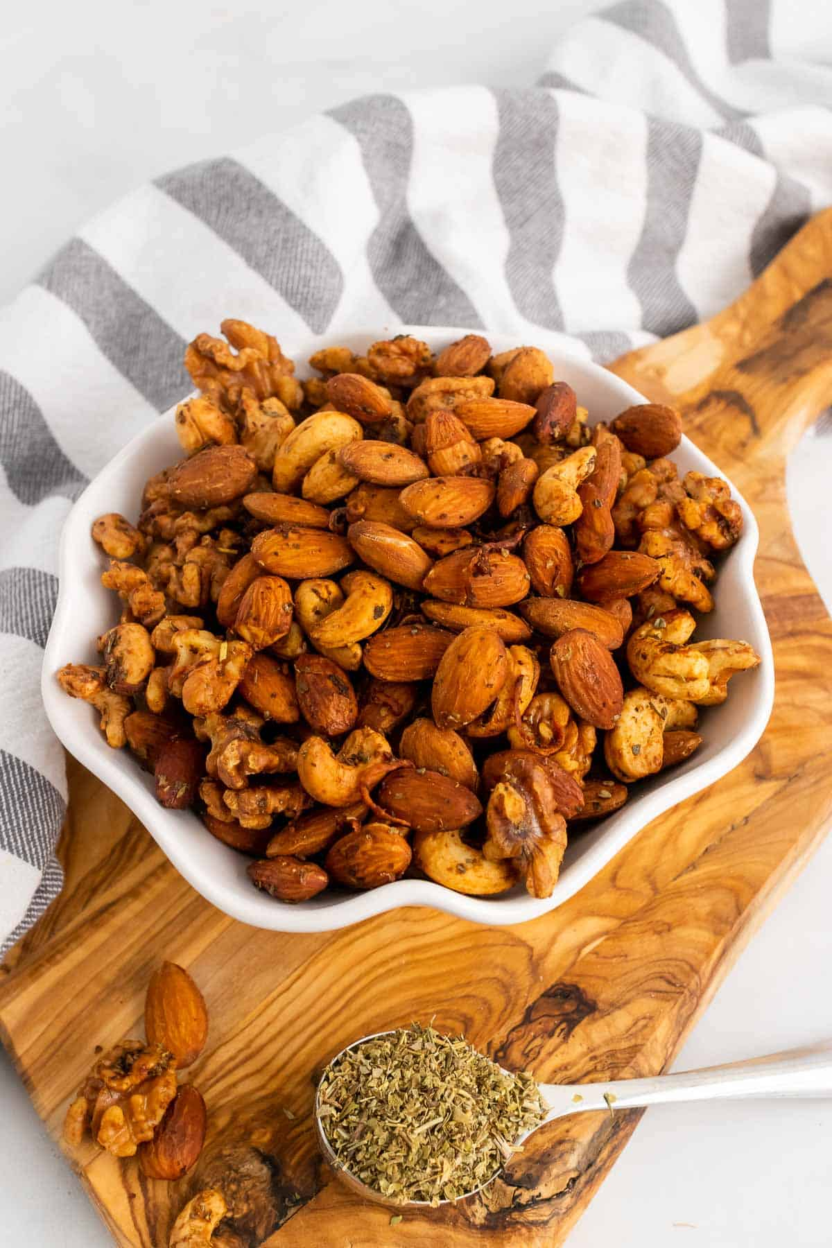 Bowl of nuts next to spoon with spice mix