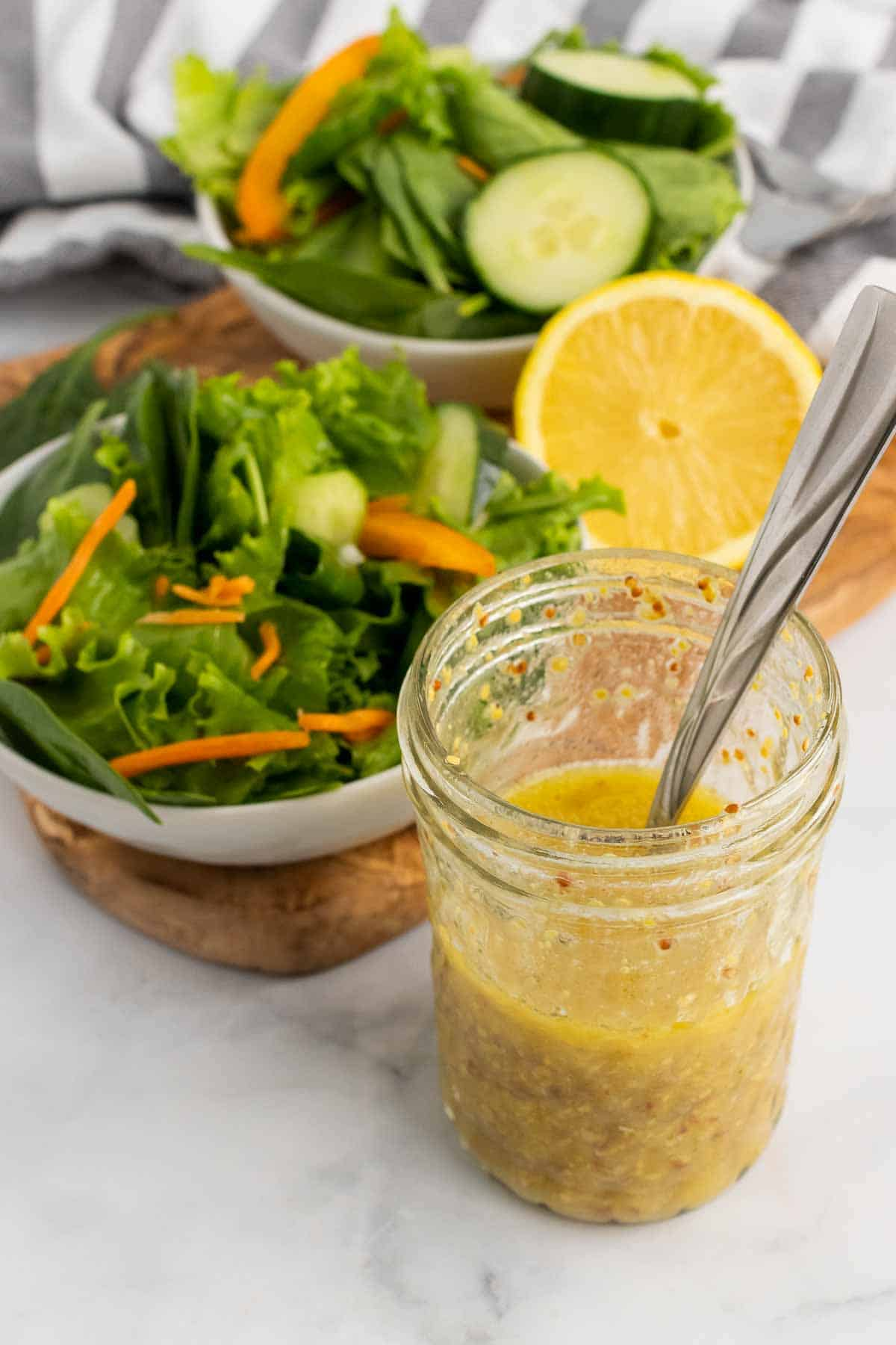 Glass jar of lemon vinaigrette in front of salad bowl