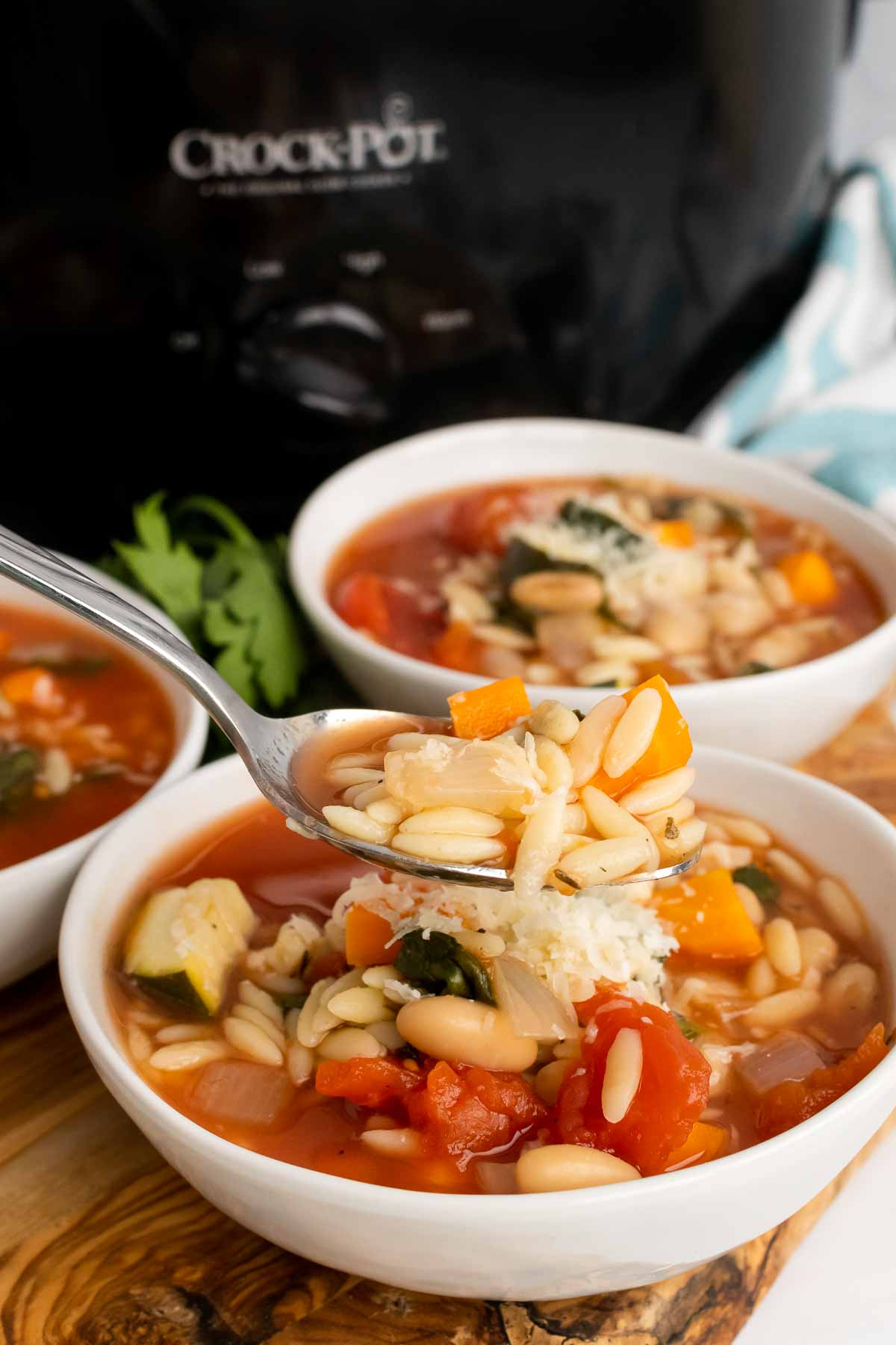 Spoon full of Slow Cooker Minestrone held over a bowl