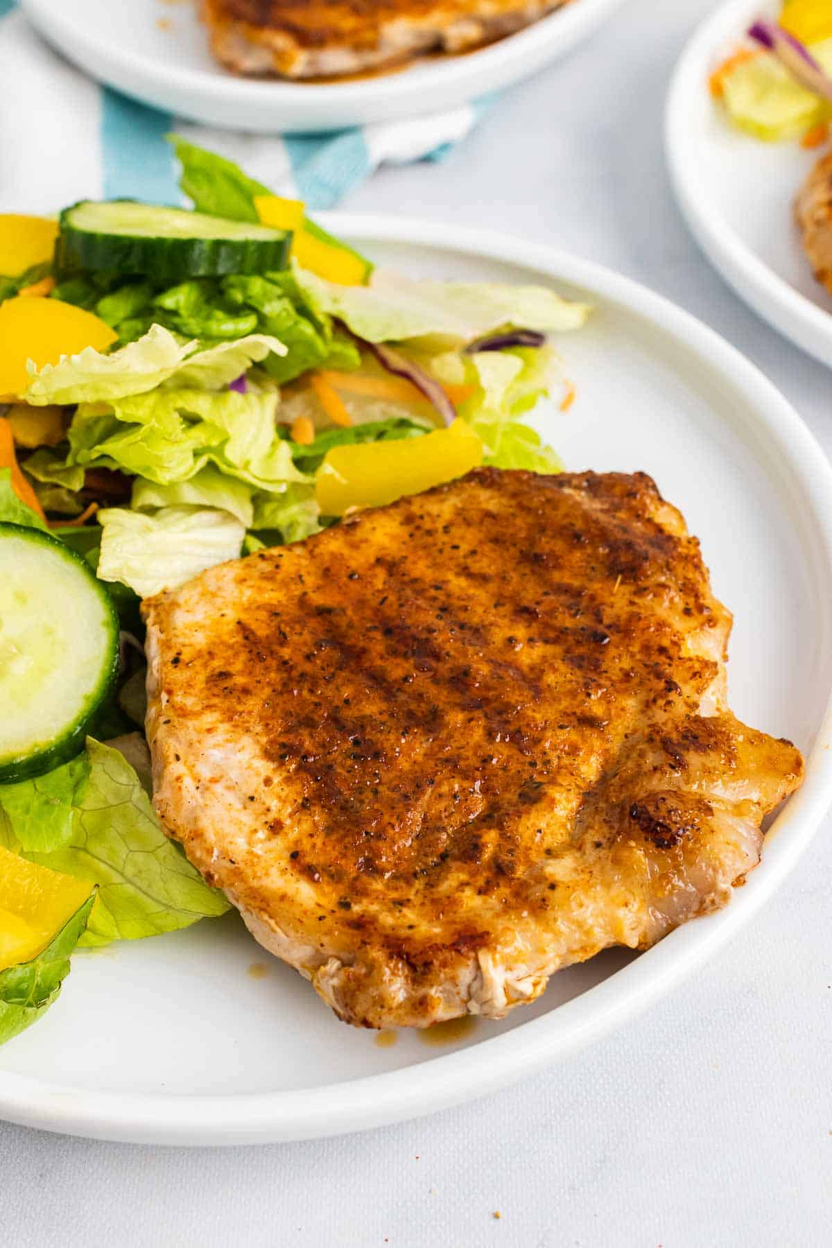 Spice-Rubbed Pork Chop on white plate with salad