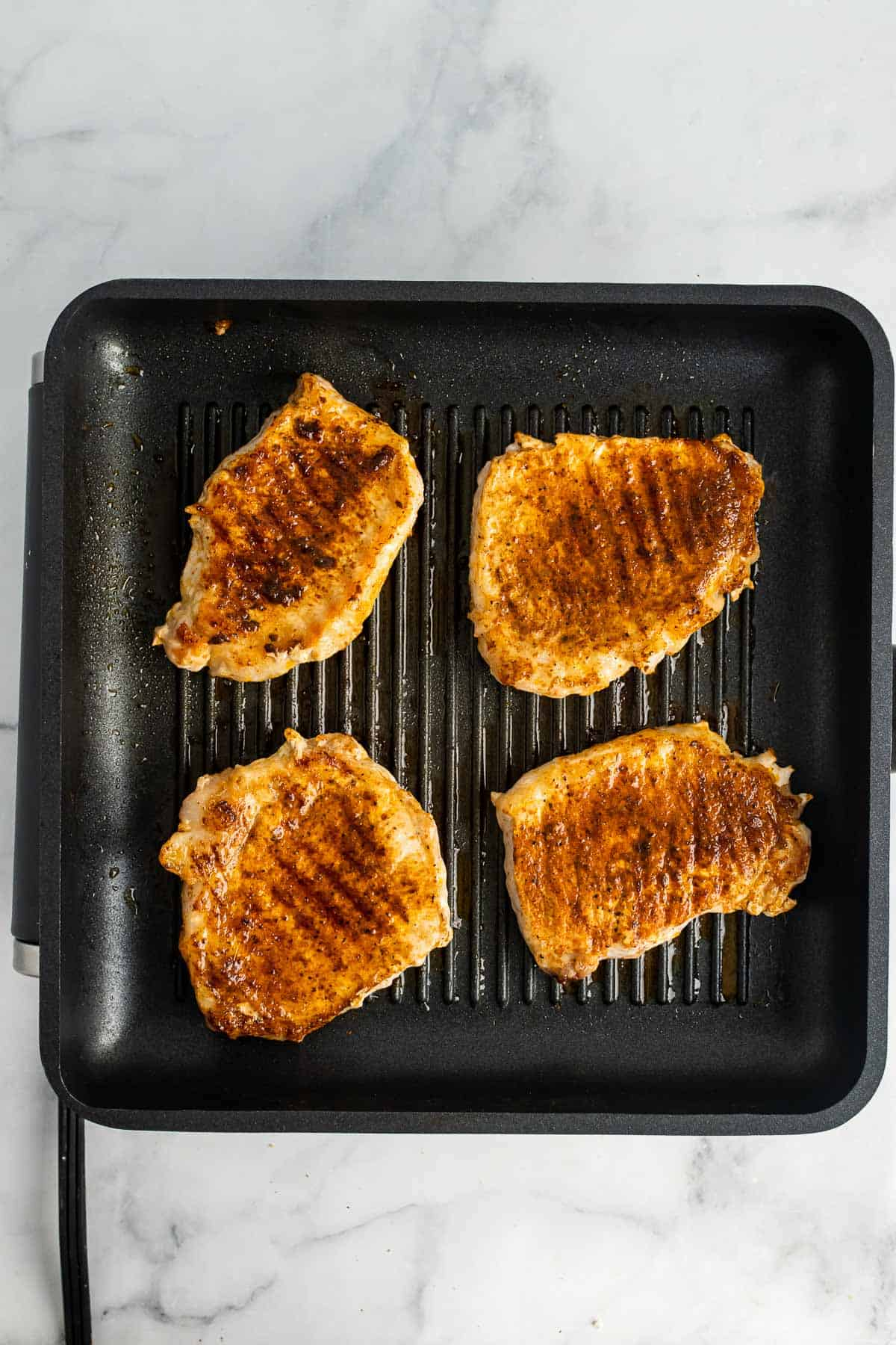 Fully cooked pork chops on a grilling pan