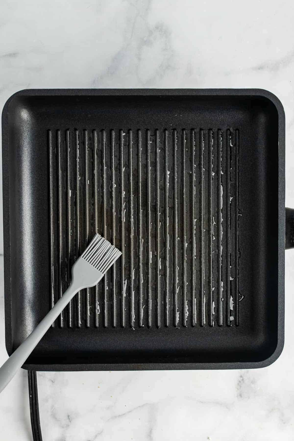 Grilling pan being coated with oil