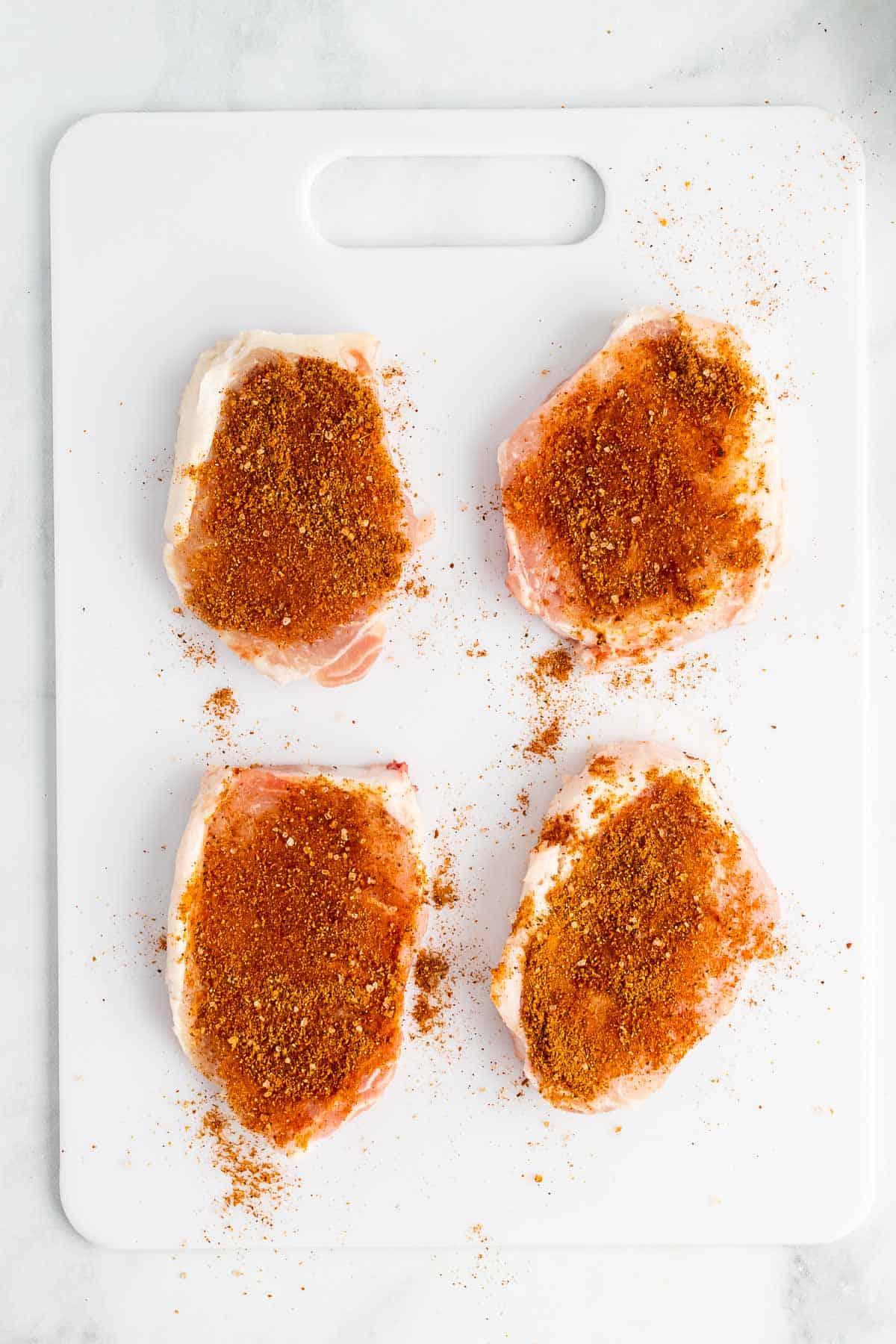4 pork chops with seasoning on cutting board