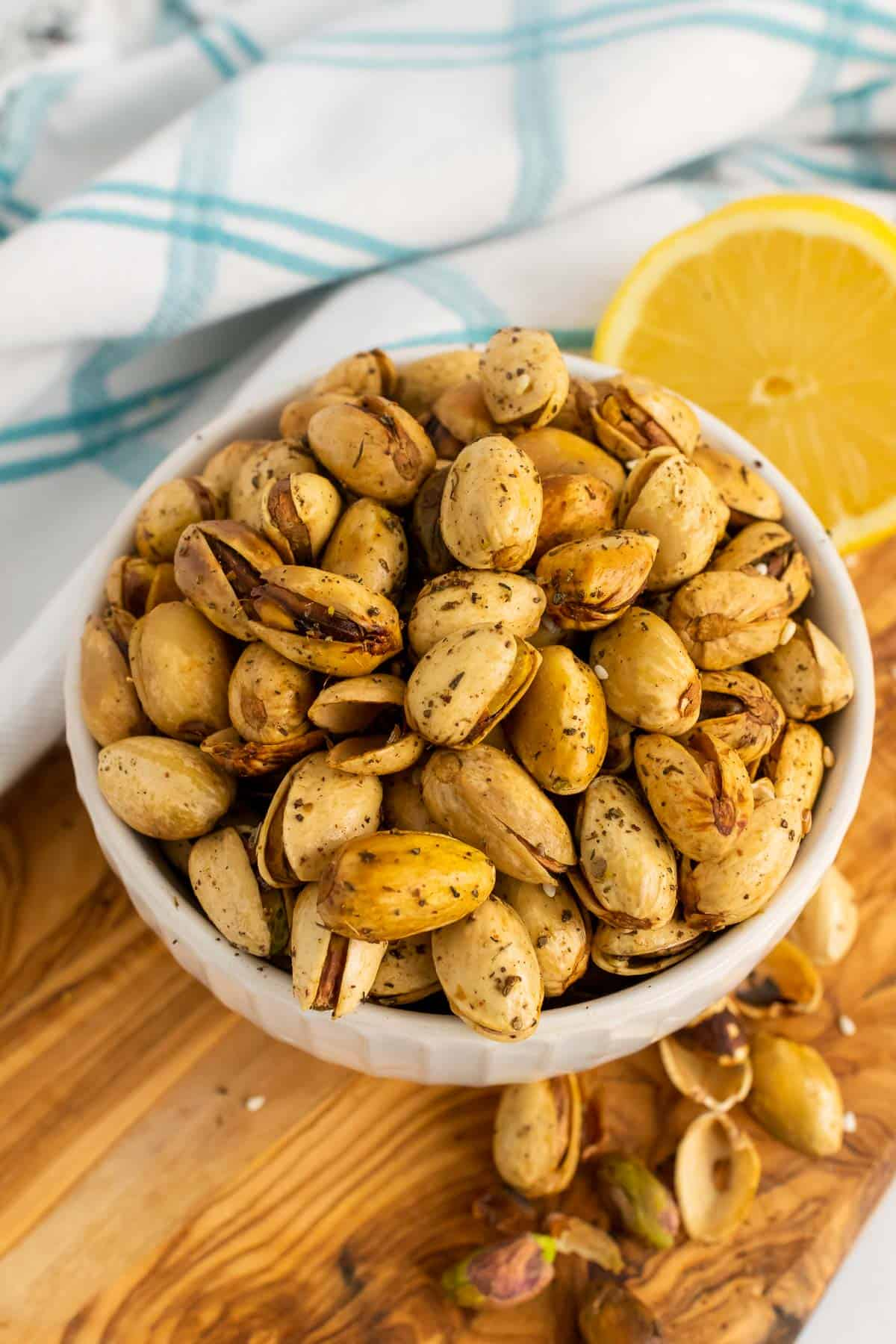 Bowl of pistachios on table with half a lemon