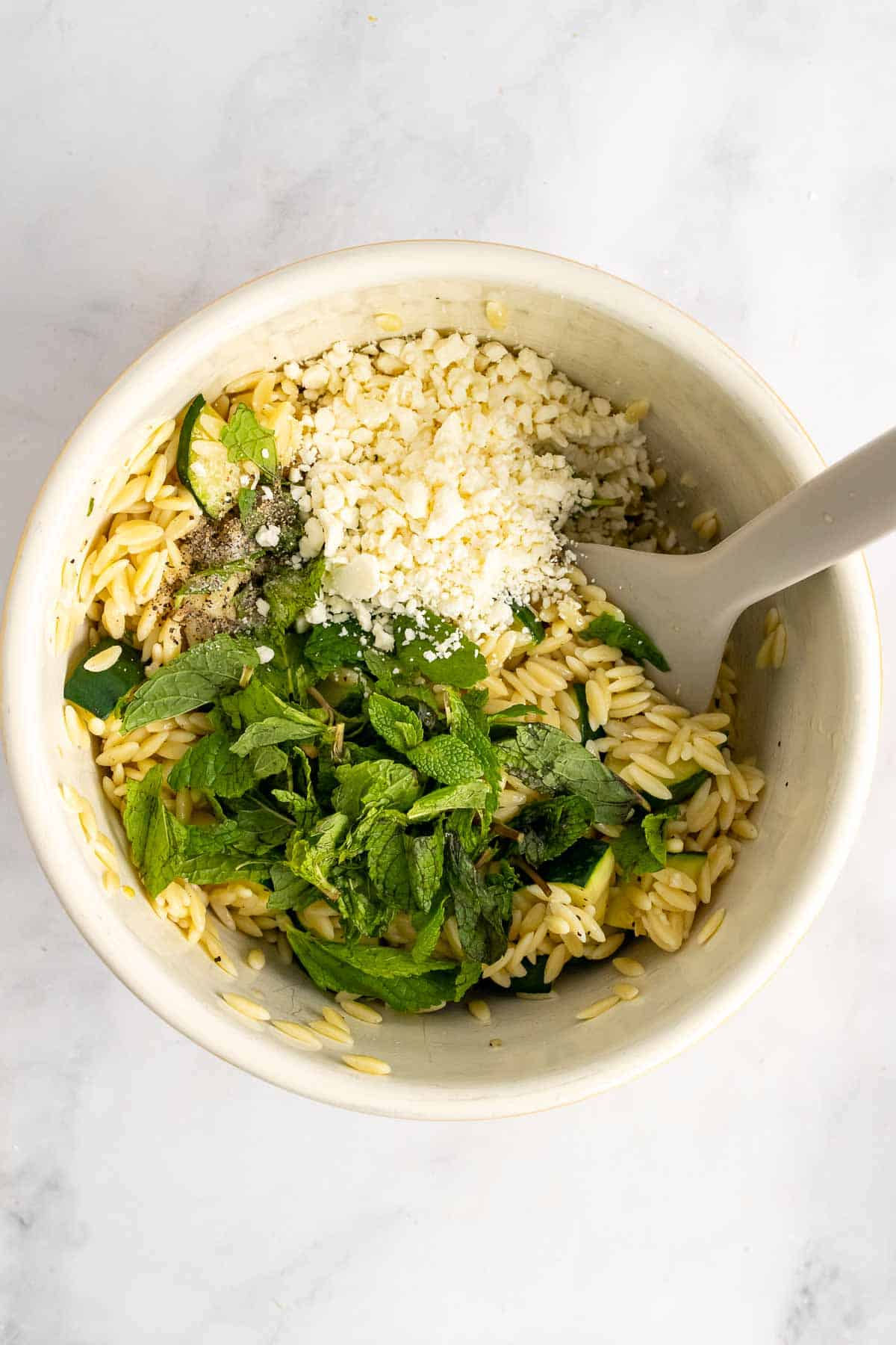 Bowl of orzo zucchini salad with faeta and mint on top