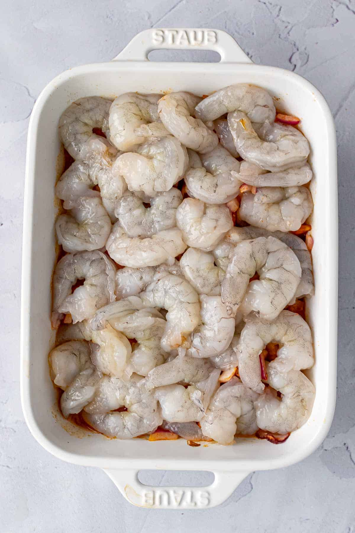 Layer of shrimp on top of the veggies in a baking dish